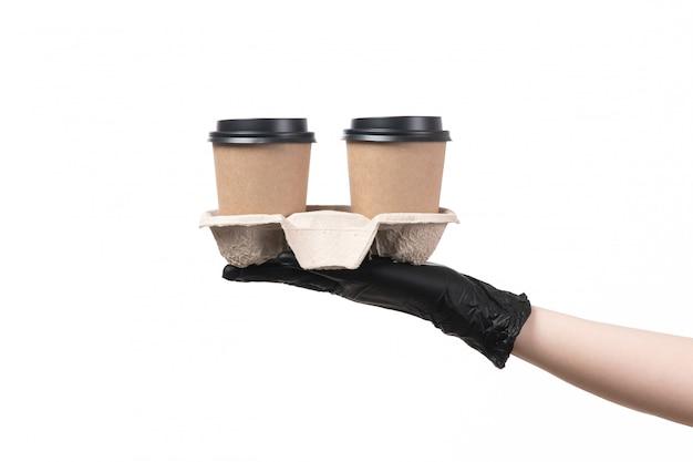 Uma mão feminina vista frontal com luvas pretas, segurando copos de café em branco