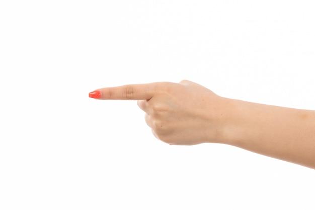 Uma mão feminina vista frontal com unhas coloridas, apontando o dedo no branco