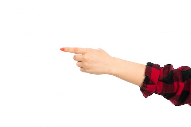 Uma mão feminina vista frontal na camisa quadriculada preto-vermelho, apontando o caminho no branco
