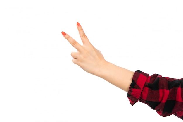 Uma mão feminina vista frontal na camisa quadriculada preto-vermelho mostrando sinal de vitória no branco