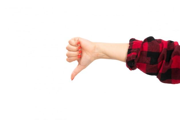 Uma mão feminina vista frontal na camisa quadriculada preto-vermelho, mostrando sinal não é legal no branco
