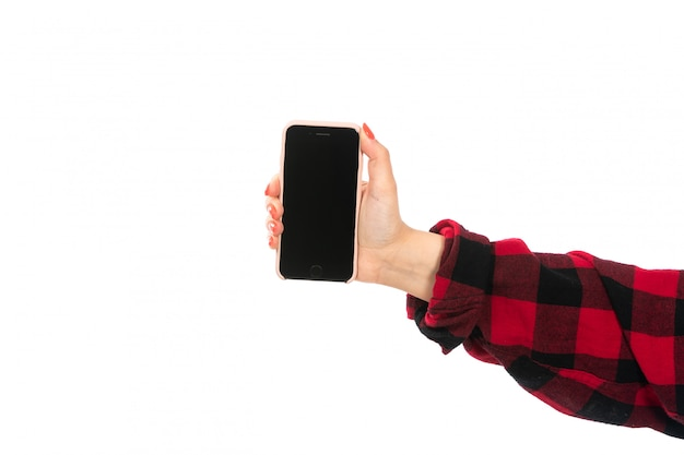 Uma mão feminina vista frontal na camisa quadriculada preto-vermelho segurando o smartphone em branco