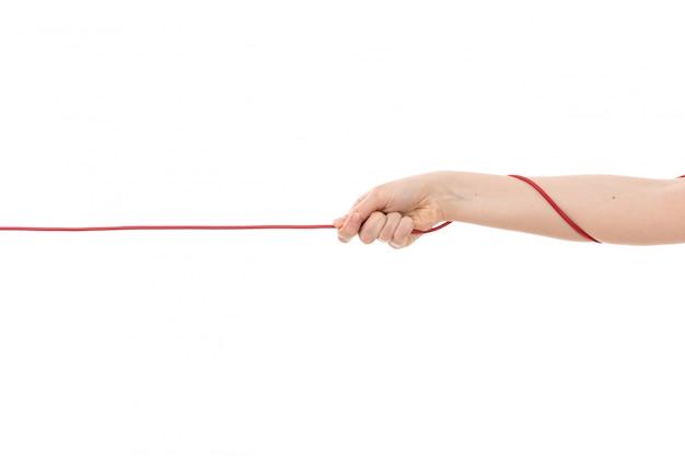 Uma mão feminina vista frontal, puxando a corda vermelha no branco