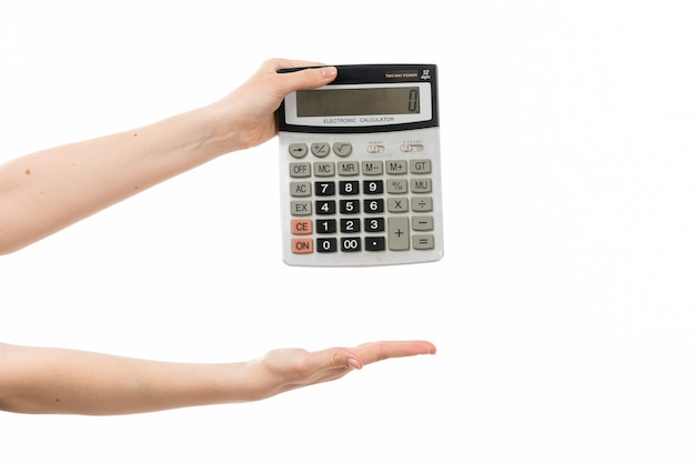 Uma mão feminina vista frontal segurando a calculadora no branco