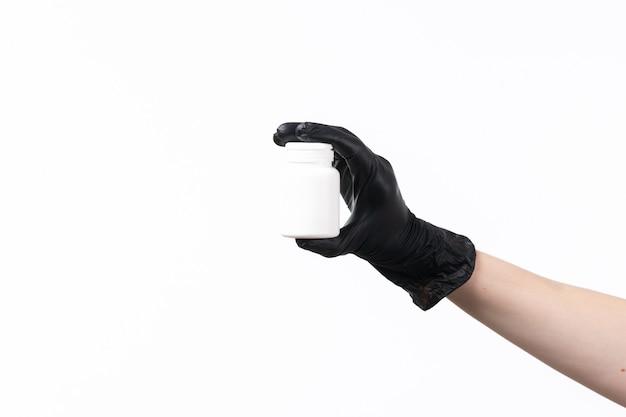 Uma mão feminina vista frontal segurando o tubo branco em luvas pretas no branco