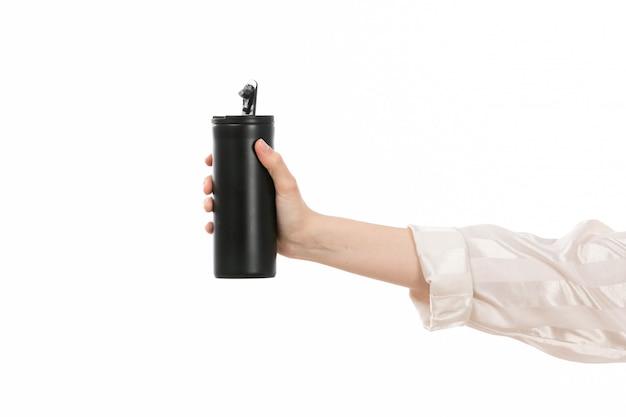 Uma mão feminina vista frontal segurando uma garrafa térmica preta no branco