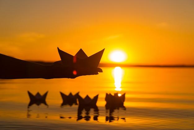 Uma mão humana detém origami na forma de um navio