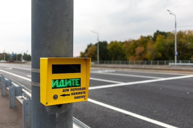 Uma mão humana pressiona um botão de faixa de pedestres com a inscrição go