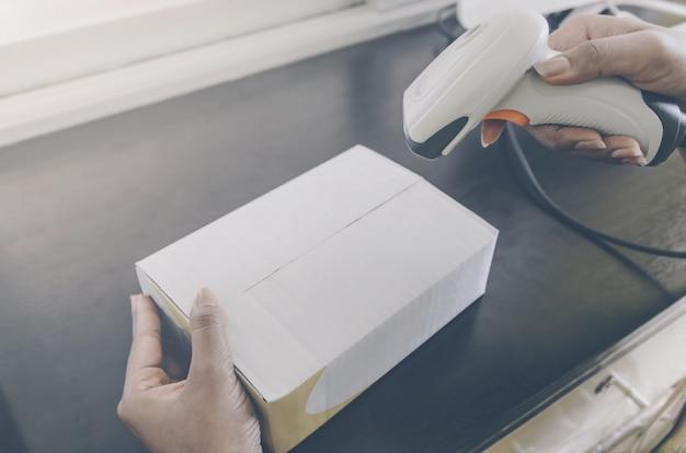 Uma mão humana que guarda o pacote com o leitor do código de barras para a entrega.