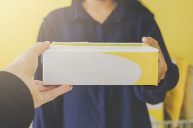 Uma mão humana que guarda o pacote e a caixa postal para a entrega e o transporte.