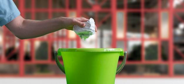 Uma mão joga o pedaço de papel amassado na cesta de lixo Foto Premium