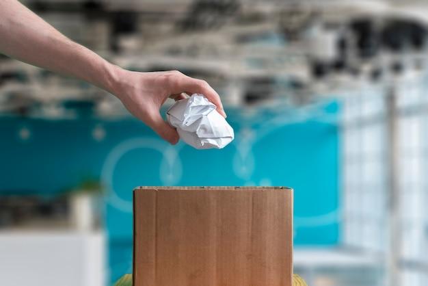 Uma mão joga o pedaço de papel amassado na cesta de lixo