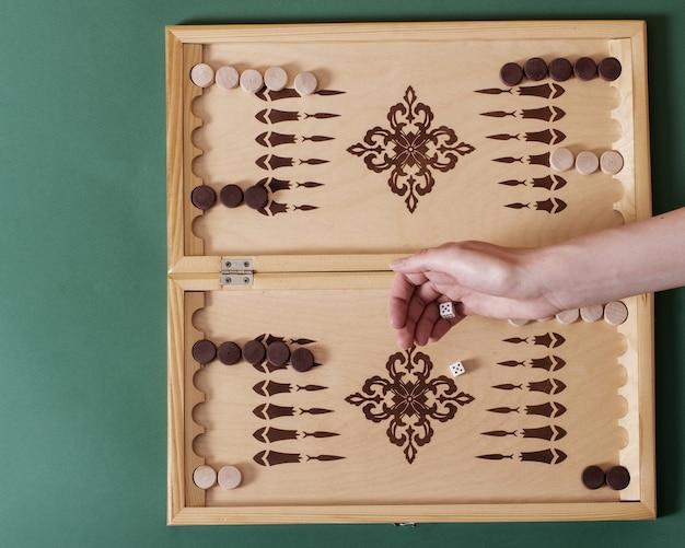 Uma mão joga um osso branco sobre um tabuleiro de gamão.