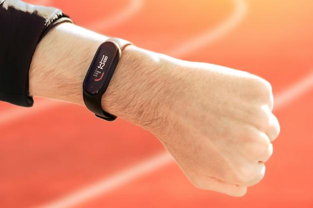 Uma mão masculina cerrada em punho com uma pulseira de fitness e o progresso do treinamento nela, pistas de corrida ao fundo