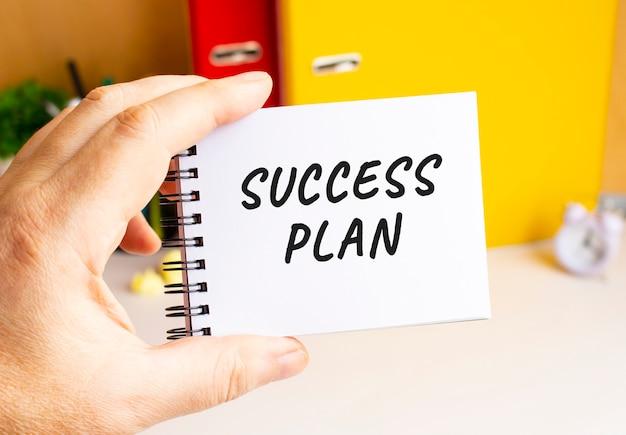 Uma mão masculina segura um bloco de notas em uma mola com o texto escrito do plano de sucesso. espaço de escritório. conceito de negócios.