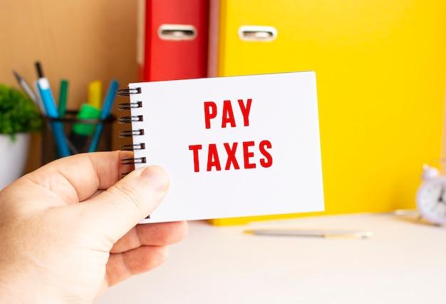 Uma mão masculina segura um bloco de notas em uma mola com o texto escrito pagar impostos. espaço de escritório. conceito de negócios.