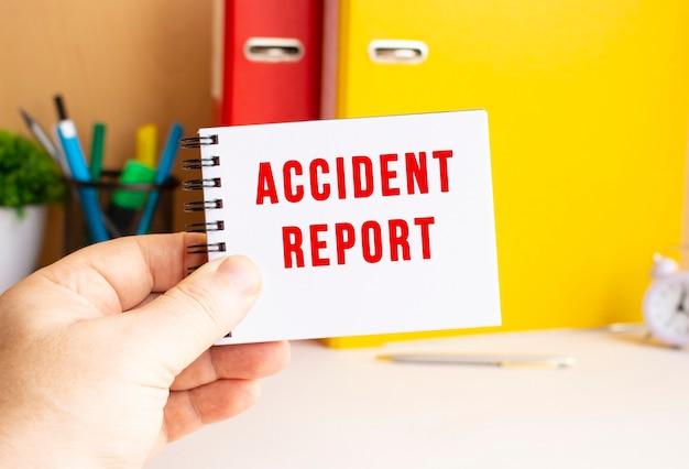 Uma mão masculina segura um bloco de notas em uma mola com o texto escrito relatório de acidente. espaço de escritório.