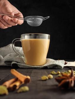 Uma mão masculina segura uma peneira para coar o chá masala sobre uma caneca de vidro com chá masala. tem especiarias na mesa