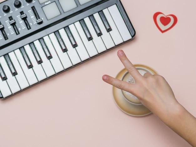 Uma mão mostra um sinal de vitória sobre uma xícara de café ao lado de um mixer de música