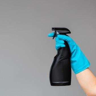 Uma mão na luva de borracha azul mantém o limpador de vidro em um frasco de spray