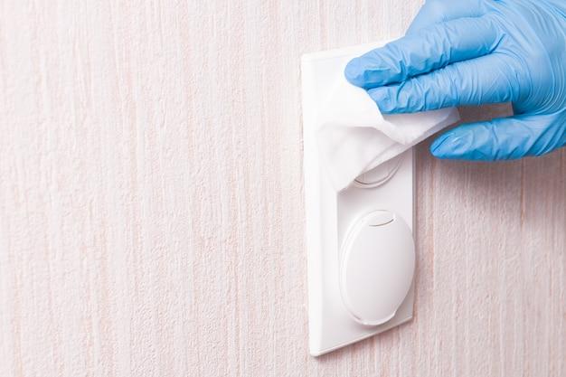 Uma mão na luva limpa um interruptor de luz com botões