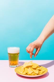 Uma mão prestes a tirar um nacho de um prato ao lado de uma cerveja em um fundo azul comida méxico