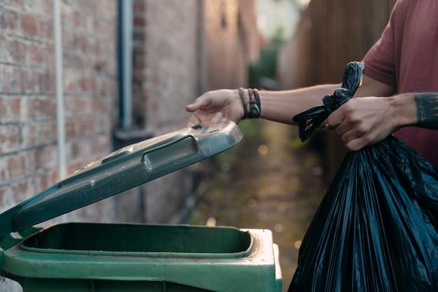 Uma mão que abre uma tampa do recipiente de lixo antes de jogar o saco de lixo no lixo