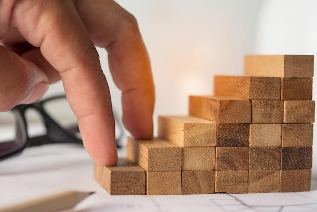 Uma mão que sobe em um bloco de madeira - um conceito de esforço.