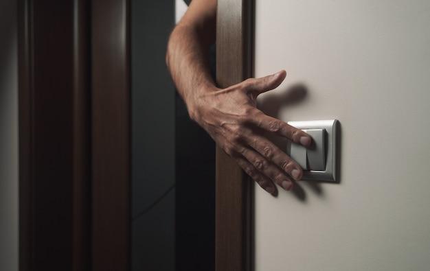 Uma mão se estende para desligar a luz da sala. tópicos de economia de energia