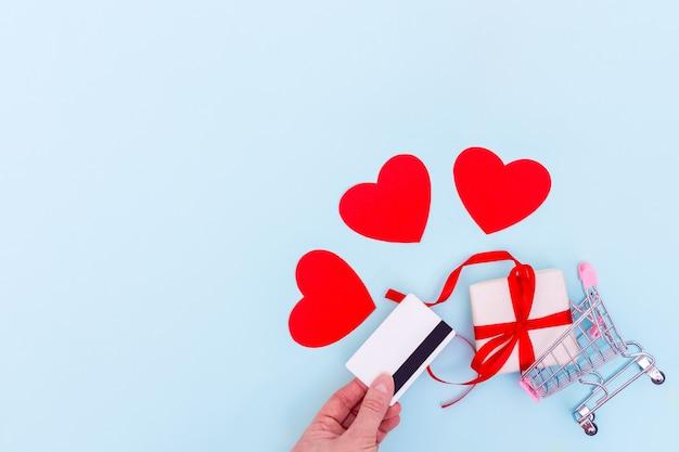 Uma mão segura um cartão de banco acima de um carrinho de compras com uma caixa de presente e corações vermelhos