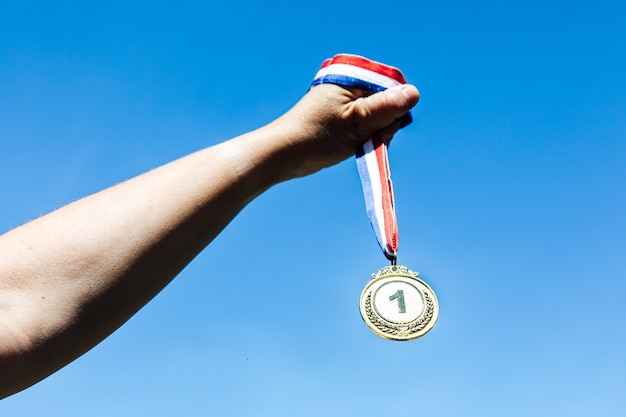 Uma mão segura uma medalha de ouro do primeiro lugar, com o céu ao fundo. conceito de vitória