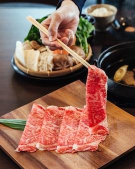Uma mão segurando premium rare slices wagyu a5 carne