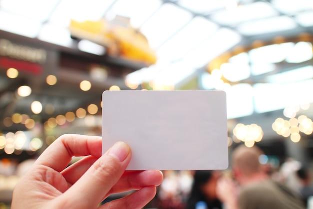 Uma mão segurando um cartão em branco com um desfoque de fundo do espaço público