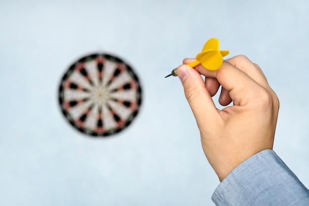 Uma mão segurando um dardo se preparando para mirar no alvo na parede azul. a mão de um homem lança um dardo no alvo.
