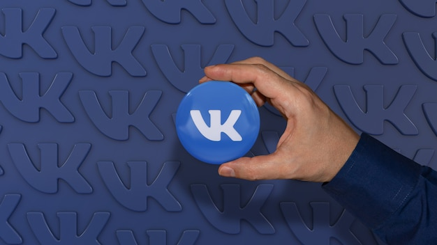 Uma mão segurando um distintivo brilhante vkontakte em azul. rede social russa.
