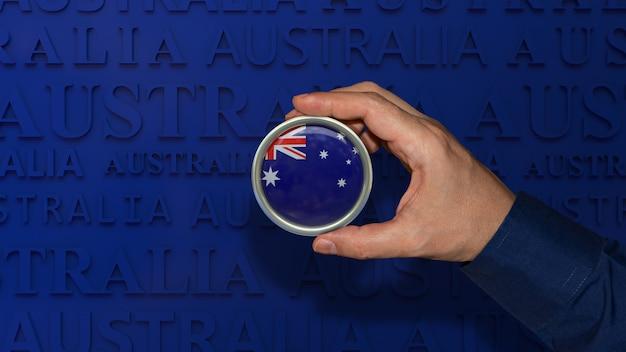 Uma mão segurando um distintivo da bandeira nacional da austrália sobre fundo azul escuro