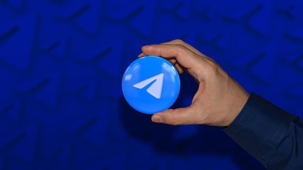 Uma mão segurando um emblema brilhante com o logotipo do serviço de mensagens sobre um fundo azul desfocado