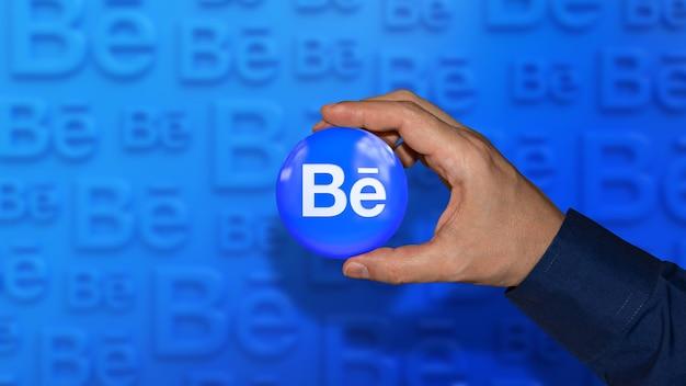 Uma mão segurando um emblema brilhante do logotipo da behance em um azul fora de foco