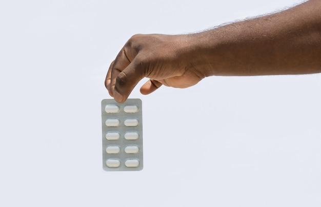Uma mão segurando um pacote de remédios com dois dedos em um fundo branco isolado