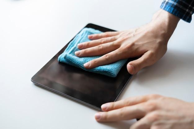 Uma mão segurando um pano e limpe a tela do monitor digital do dispositivo