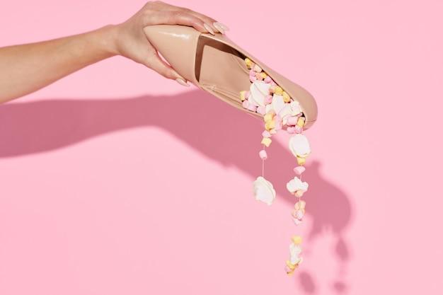 Uma mão segurando um sapato feminino em um fundo rosa isolado