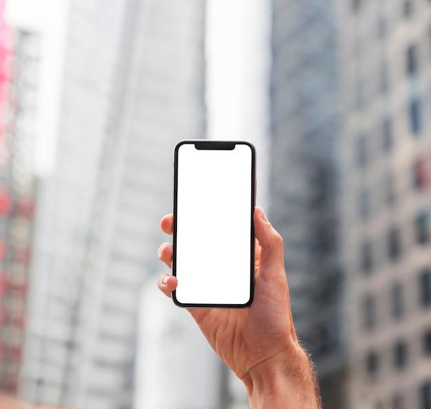 Uma mão segurando um smartphone em uma rua da cidade