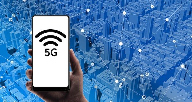 Uma mão segurando um telefone celular 5g, plano de fundo da cidade, edifício e conexão sem fio, conceito de rede 5g, internet móvel de alta velocidade