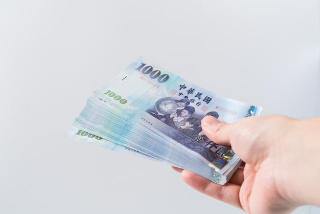 Uma mão segurando uma nota de 1000 dólares de taiwan.