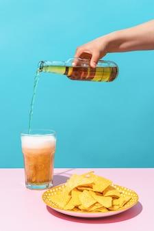Uma mão servindo uma cerveja ao lado de um prato de nachos em um fundo azul comida méxico e verão