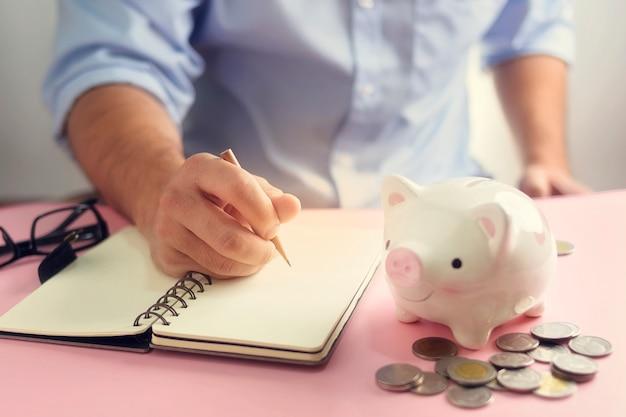 Uma mão tomando nota para lista de despesas com moedas de dinheiro e cofrinho. poupar dinheiro para o conceito de investimento futuro.