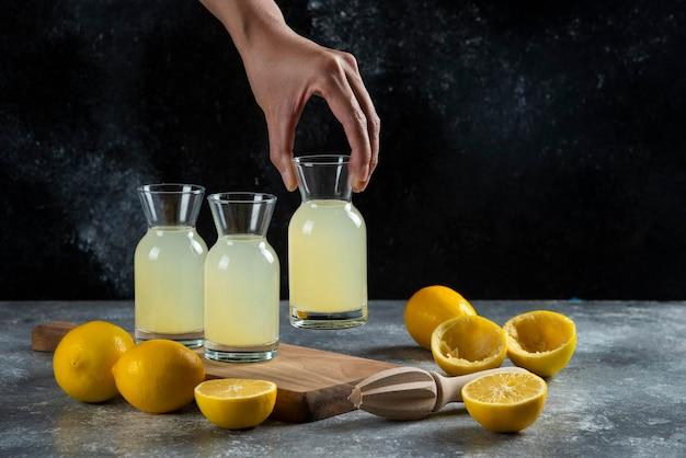 Uma mão tomando um pote de suco de limão.