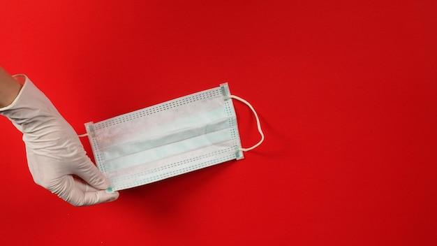 Uma mão usa luvas de látex ou luvas médicas brancas e segurando uma máscara facial sobre fundo vermelho