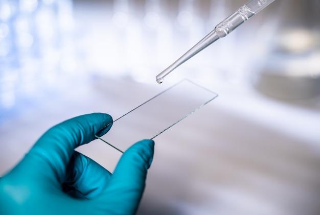 Uma mão usando uma luva azul segura uma lâmina de microscópio com o vírus # 7, escrito no marcador.