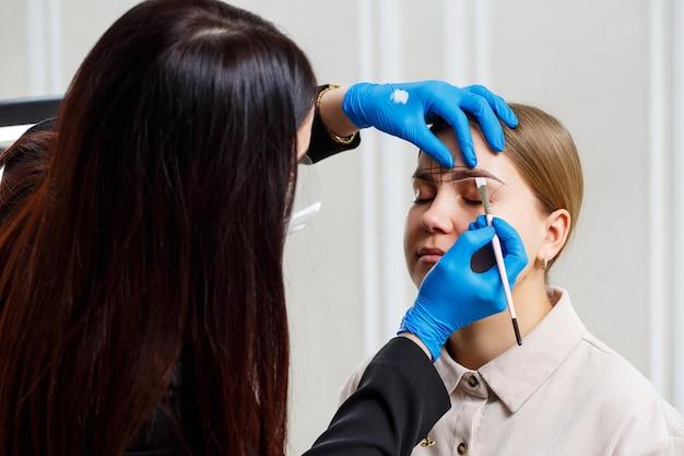 Uma maquiadora permanente desenha um esboço das sobrancelhas no rosto de sua cliente.